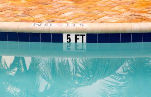 """A pool with a """"5 ft"""" sign."""
