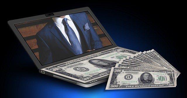 $500 bills on a laptop