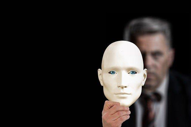 Businessman partially hiding behind a mask