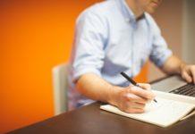 Man writing something down while working on his laptop